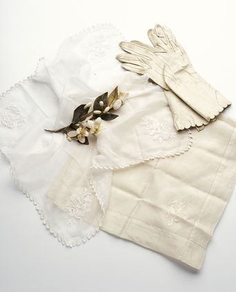 Wedding accessories including Hannah and Alfred's handkerchief, Hannah's gloves and sprig of wax orange blossom.
