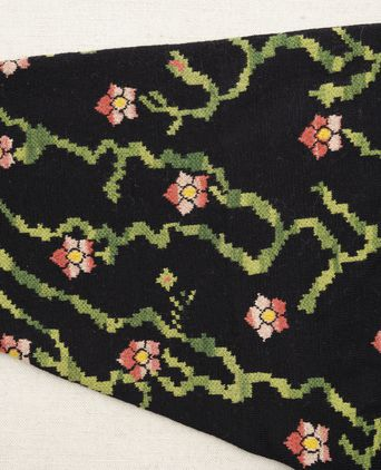 Close up of deeply inset sleeve with all over pattern of pink and yellow flowers on space-dyed green stem and meander