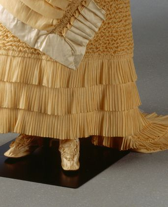 Detail of kilting or pleating along the bottom of Hannah's dress
