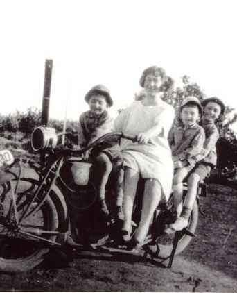 Luigia Pastega and her sons on a motorbike.